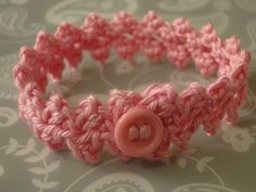 A pink buttonbraid bracelet in sports weight yarn.
