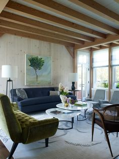 In the living room, the clean lines of the more contemporary furnishings play up the post-and-beam structure | archdigest.com