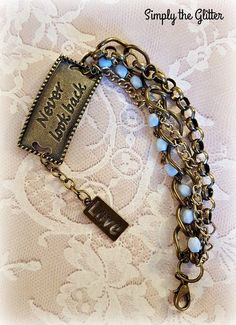 """This is a beautiful bracelet made using a brass stamped connector link """"NEVER LOOK BACK"""". I used light blue rosary beads along with 3 different kinds of chunky brass chains to finish off this piece. Hanging from the connector link is a brass LOVE charm. A brass lobster clasp makes it easy on/off. After spending many enjoyable hours repurposing items from broken necklaces, this is now ready to be reloved in a fresh new piece! All handmade items may have some variations in color and finis..."""