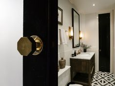 Brass hardware accents a black and white bathroom.