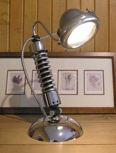 This old school shock lamp has a vintage brass and chrome headlight, chrome Harley Davidson shock, and an HD chrome FL hub cover. Chromatic!