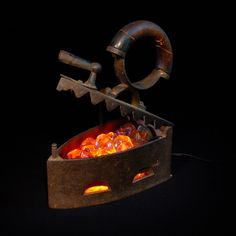 In this ongoing series of light fixtures, fiery, flickering bulbs illuminate a bed of glass embers nestled within the cast iron bellies of 19th century coal irons.   $275