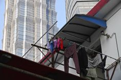 A worker family's clothes hang out to dry from ledges of their temporary housing units near the Shanghai Tower construction site.