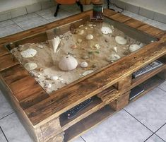 A DIY pallet wood glass display coffee table idea for the avid beachcomber! Leaves plenty of space to create a great beach scene with sand and shells. Featured on Completely Coastal. Pallet Furniture And Decor, Diy Pallet Furniture, Diy Furniture Projects, Diy Home Decor Projects, Diy Pallet Projects, Decor Ideas, Wooden Furniture, Furniture Design, Diy Ideas