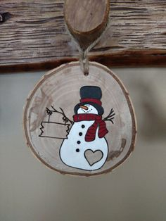 Tree slice ornament with snowman. All wood discs are from fallen limbs on our property that I let dry out, slice into discs and then sand. Each disc has its own markings, knots and bark details - nature is consistently random so no two ornaments are alike. The snowman is holding a