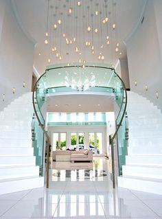 U-shaped double staircase, nice white finish, and glass railing match well together. The hanging lights and design amidst the tiling give off very nice feeling to the home.