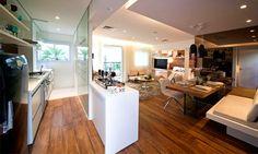 Apesar de não haver paredes nesse apartamento de 50 m², os ambientes estão bem definidos. A bancada deixa claro onde é a cozinha, ao mesmo tempo em que a estante vazada define o quarto da sala. A TV pode servir aos dois ambientes, por meio da rotação. A integração deixa o ambiente mais amplo, dando sensação de espaço. Projeto da Smart Décor, de Fernanda Marques