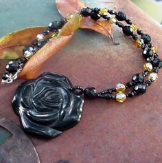 Large statement necklace. Flower pendant is carved from black stone and accented by jet black fire polished glass and yellow crystals as bright...
