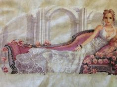 """Almost done with """"Abbi"""" by Heritage Crafts. The lace in the gown is gorgeous, not to mention the beautiful flowers surrounding her on the couch. Cross Stitch Gallery, Heritage Crafts, Cross Stitch Supplies, Cross Stitching, Fabric Patterns, Cross Stitch Patterns, Beautiful Flowers, Needlework, Gown"""