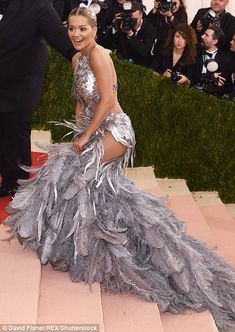 Struggling to soar: Rita Ora opted for a daring and quirky look for her turn on the Met Gala's red carpet - wearing a gown made entirely of silver feathers, which caused an unfortunate hitch when it came to scaling the stairs at the landmark