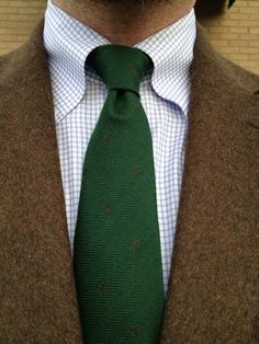 Brown tweed jacket, white shirt with blue check, green tie, light grey pants