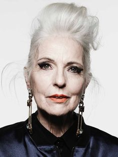 Older punk rocker woman, white hair, cat-eye makeup, artist earrings
