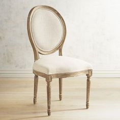 The aristocratic Eliane is a direct descendant of Louis XVI's classic dining chair. Crafted of solid European oak, it features the same iconic oval back, tight raised seat, corner medallion molding and turned legs as its regal ancestor. Hand-upholstered fabric and a refined whitewash finish complete the family resemblance. All for beaucoup francs less than the original.