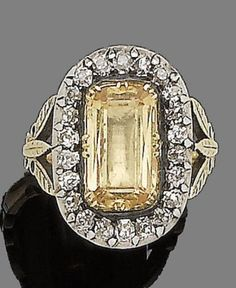 A 19th century topaz and diamond ring The rectangular step-cut topaz in a foiled closed-back setting, within a cushion-shaped diamond surround, to foliate trifurcated shoulders, diamonds approx. 0.60ct total
