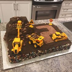 Digger Cake   Dirt digger cake. Chocolate buttercream and chocolate cookie dirt. Chocolate rocks around the edging. Chocolate sponge boulders.