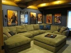 Home theater room, with a big couch and popcorn machine and movie posters on the. Home theater room, with a big couch and popcorn machine and movie posters on the walls bug shelf fo At Home Movie Theater, Home Theater Rooms, Home Theater Design, Home Theater Seating, Cinema Room, Movie Theater Basement, Theater Seats, Big Couch, Gameroom Ideas