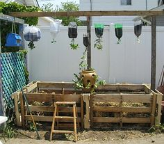 Todays pallet fix: Palletsrepurposed to contain a compost pile. Also: Plastic bottles used as planters. Lots of reuse pictured here! (photo via The Reuser: A study in reusearchive)