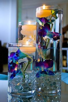 Floating candles with blue and purple orchids. www.reflectionsweddings.ca