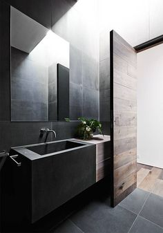 Honed charcoal tiles gives the impression of solidity and sophistication within this bathroom which is as been balanced with a large sky light that allows plenty of natural light.