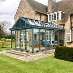 Modern grey aluminium conservatory and bespoke tiled roof section, built on a traditional stone house