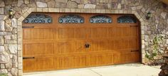 Medium / Light wood grain steel garage door with handles hinges ans iron arch windows. see more at www.ontracdoors.com