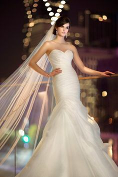 D1460 This airy soft Royal Organza wedding gown features a stunning sweetheart neckline, ruched bodice and dropped waist, and a flowing skirt with fabric pickups at the hip. Lace up  or zipper back under covered buttons available.