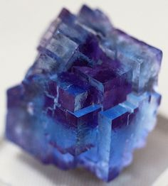 "Fluorite (CaF2) Blue Fluorite with Phantom Purple - Macro view of a very small but special fluorite crystal speciment, only 1 1/4"" tall, captured through the glass display case. This shows a clear blue outer row of translucent blue cubes grown over an initial purple crystal.from cobalt123. I really like  blue Fluorite."