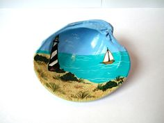 Lighthouse clamshell coastal home decor, hand painted seashell art, sailboat and the sea. $14.75, via Etsy.