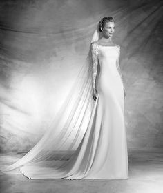 VASILY style: Flared crepe wedding dress with long sleeves. Bodice with off-the-shoulder neckline and long sleeves in Illusion tulle embellished with rebrodé lace appliqués. Transparent straps in illusion tulle.