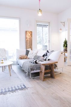 White Scandinavian living room with wide wood planks on the floor, white sofa and graphic cushions