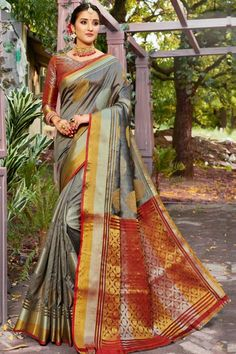 Grey banarasi silk saree with red banarasi silk blouse. Embellished with woven zari work. Saree with V Neck, Quarter Sleeve. It comes with unstitch blouse, it can be stitched to 32 to 58 sizes. #saree #IndianSaree #Sareeonline #Festivalwear #PartyWear