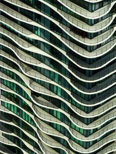 Ritme in de vormgeving van de gevel van dit gebouw. Golvende lijnen, balkons, kleur