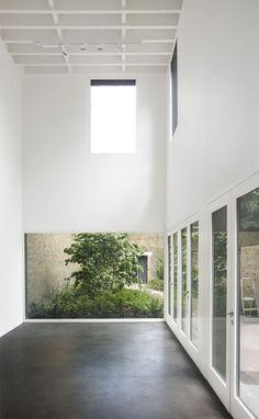 blank white walls + lush greenery + aged brick