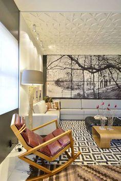 Estar em Casa - Lisiane Wendel Corrêa e Simone Bertuzzo. A luminosidade e os tons crus característicos do estilo escandinavo entram em cena. A parede atrás do sofá ganha uma composição de seis telas em suede de 137x140cm. O piso de mármore é parcialmente coberto pela sobreposição de tapetes kilim.