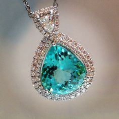 18K White Gold Pendant with a 8.90 carat Pear-Shaped Paraiba Tourmaline surrounded by a Double Row of Round Brilliant Cut Diamonds #phenomenal
