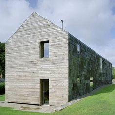 Slate roof tiles extend down the exposed north facade of this house in Wales by London studio Feilden Fowles.