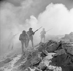 'Australians storm a strongpoint'. A posed portrait of Australian troops advancing during the Second Battle of El Alamein, 3 September 1942.