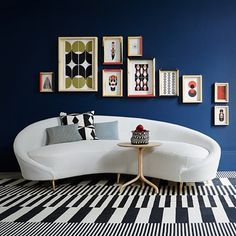 Taking the classic combination of black and white as her starting point, deputy decoration editor Ruth Sleightholme created graphic schemes  enlivened by shots of colour. Here, a collection of artwork by Frederico Pepe works well against a navy blue wall.