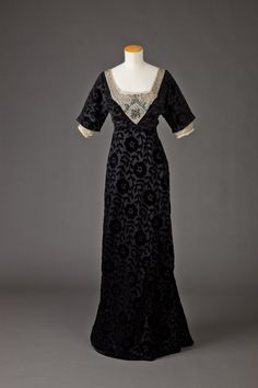 1910-15 Black silk voided velvet evening dress with large floral and leaf motifs. Low square neckline in front; low v neckline in back. Neckline outlined with ecru net solidly covered with silver, black and white beads and rhinestones. Narrow almost hobble skirt, train.