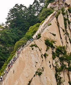 """Mt. Huashan Heavenly Stairs, China. Eventually, the steep, deadly """"heavenly stairs"""" stop, and this becomes the most hellish horizontal walk in the world—a three-plank-wide walkway with only a chain to hold onto, flush against the wall of flat rock. When that's done, there's another set of meandering, mountainside stairs. If you get to the top of Mount Huashan, you'll discover that """"heaven"""" is a remote teahouse with a terrific view."""