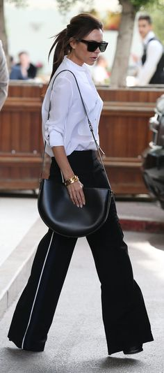 Victoria Beckham in wide-leg trousers and a white blouse.