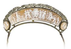 A shell cameo diadem, circa 1820-1830. The long central shell panel depicting the three Graces at the center of a festival of music and dance, flanked by two similarly carved oval cameos, within a beaded surround and decorated to the top with a garland of rose and foliate detail. Image and via Bonhams.
