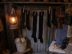 Primitive Christmas fireplace with long old black stockings. Barn lamp and sock cat. Sweet Liberty Homestead candle dryer.