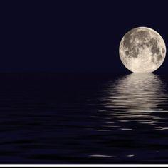 Full moon rising above water.