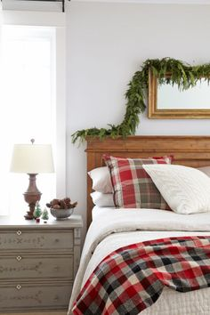 Bowl of pine cones on the nightstand, garland draped over headboard and plaid bedding make this bedroom feel Christmassy