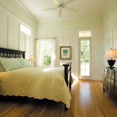 Beautiful room! Dark furniture, yellow coverlet, blue pillows, white planks, light green at top of wall