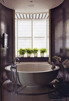 Round free standing tub with saucer base, brushed metal exterior, white interior, standing plumbing hardward, high gloss gray walls, window across entire end of room, 4 white planters with greenery on window sill, simple yet elegant