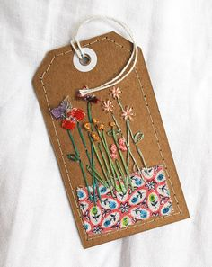 Hand-stitched pretty label on brown card using vintage embroidery cotton, and some wonderfully colourful vintage feedsack.
