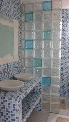 Un meuble-lavabo et une douche entièrement recouverts de carrelage mosaïque composé de diverses teintes de bleu. Un mur de blocs de verre, dans lequel quelques blocs bleus ont été insérés, sépare le coin douche du reste de la salle de bain. Le sol est recouvert de carreaux grisâtres.