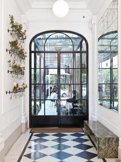 Pasillo de entrada de Casa Cavia con banco de mármol, piso de cerámicos en blanco y negro, y gran puerta de hierro y vidrio que da paso al jardín.